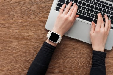 Cropped view of girl with smartwatch typing on laptop keyboard on wooden background