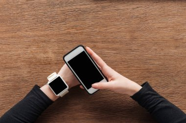 Cropped view of girl with smartwatch holding smartphone with with blank screen on wooden background