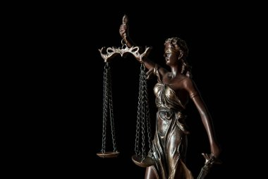 close up of bronze statuette with scales of justice isolated on black