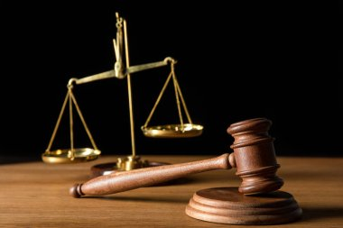selective focus of vintage golden scales and gavel on wooden table isolated on black