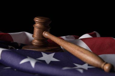 wooden gavel on american flag isolated on black
