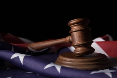 wooden brown gavel on american flag isolated on black