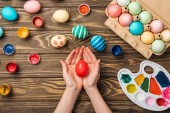 Fotografia vista superiore della holding della donna dipinta uovo di Pasqua al tavolo di legno con vernici e colori