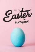 blaues Hühnerei auf rosa Hintergrund mit frohen Ostern für alle Schriftzug