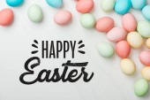 Fotografie top view of multicolored chicken eggs on grey background with happy Easter black lettering