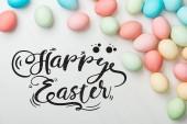 Draufsicht auf bunte Hühner bemalte Eier auf grauem Hintergrund mit fröhlichem osterschwarzem Schriftzug