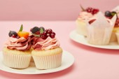 two plates with sweet cakes on pink surface
