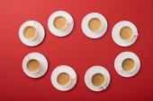 Nejlepší pohled na bílé šálky s chutnou kávou na talířcích na červeném pozadí
