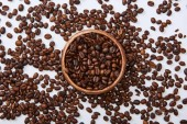 top view of tasty coffee roasted beans in wooden bowl on white background