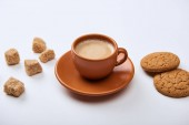 delicious coffee with foam in cup on saucer near brown sugar and cookies on white background