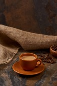 hot coffee in cup on saucer on marble surface near sackcloth and beans