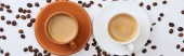 Fotografie top view of coffee in white and brown cups on saucers near scattered roasted beans, panoramic shot