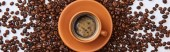 panoramic shot of delicious coffee in brown cup near scattered roasted beans on white background