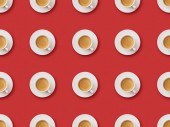 seamless pattern with coffee in cups and saucers on red background