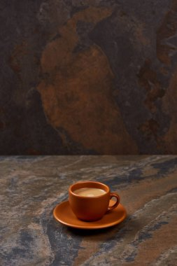 delicious coffee in brown cup on saucer on marble table