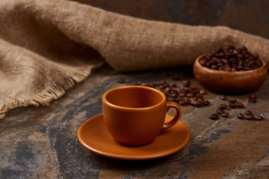 brown cup on saucer on marble surface near sackcloth and coffee beans