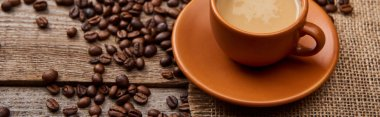 panoramic shot of coffee beans near cup of coffee on wooden background