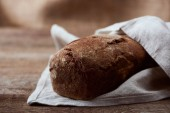 fresh baked brown bread in white napkin on wooden table