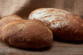 close up view of tasty fresh bread loaves on wooden table