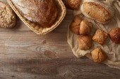 top view of fresh baked bread in wicker basket and buns on cloth on wooden table
