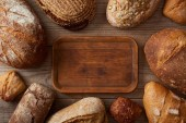 top view of fresh homemade loaves of bread around wooden empty chopping board