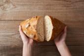 oříznutý pohled na ženu držící čerstvý pečený chléb na dřevěném stole