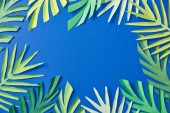 Photo top view of green paper cut tropical leaves on blue background with copy space