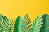Fotografie pohled shora na papír odřízený exotický zelený palmový listí na žlutém pozadí s prostorem pro kopírování