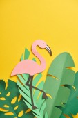 pohled shora na papír nakrájejte zelené palmové listy a roztomilý plameňák na žlutém pozadí