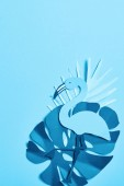 top view of blue minimalistic paper cut palm leaves and flamingo on blue background with copy space