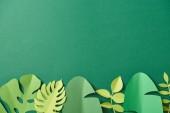felülnézet egzotikus papír vágott pálmalevelek zöld háttérrel a másolási tér