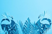 top view of blue paper cut palm leaves and flamingos on blue background with copy space