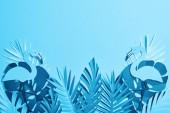 felülnézet kék papírra vágott pálmalevelek és flamingók kék háttér másolási Space