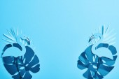 Fotografia vista dallalto della carta esotica blu taglia foglie di palma e fenicotteri su sfondo blu con spazio di copia