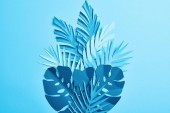 Photo top view of blue exotic paper cut palm leaves on blue background with copy space