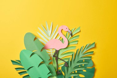 top view of paper cut green palm leaves and pink flamingo on yellow background with copy space