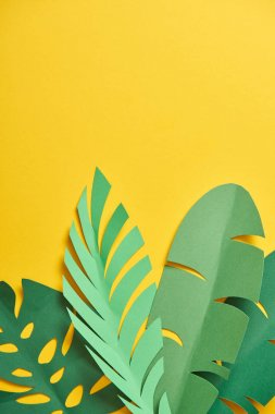Top view of paper cut exotic green palm leaves on yellow background with copy space stock vector