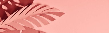 Panoramic shot of paper cut palm leaves on pink background stock vector