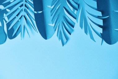 Top view of blue minimalistic paper cut palm leaves on blue background with copy space stock vector