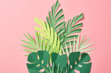 top view of green palm leaves on pink background with copy space