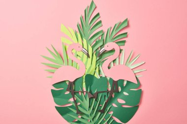 Top view of paper cut flamingos on green palm leaves on pink background stock vector