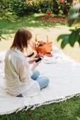 szőke lány ül takaró kertben, és miután piknik a napsütéses napon, miközben a smartphone