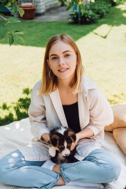happy blonde girl sitting on blanket in garden with adorable puppy at sunny day
