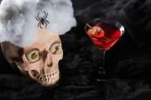 Roter Cocktail in der Nähe von gruseligen Totenkopf mit Spinne auf schwarzem Hintergrund