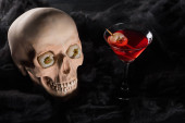 red cocktail near spooky skull on black background