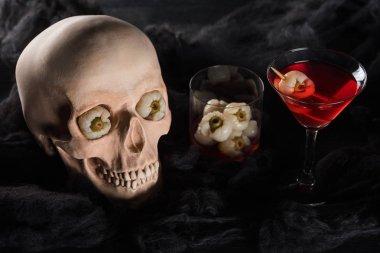 Red cocktail near creepy skull on black background stock vector