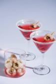 rote süße Halloween-Cocktails mit Dekoration in Gläsern auf weißer Oberfläche