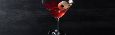 panoramic shot of red decorated Halloween cocktail on black background