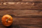 pohled na malou oranžovou tykev na hnědém dřevěném povrchu s prostorem pro kopírování