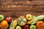 Fotografie top view of fresh apples, pumpkins and sweet corn on wooden surface with copy space